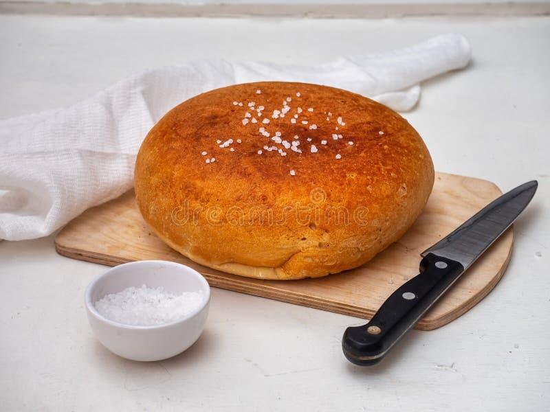 Домодельный хлеб на деревянной unpainted доске с грубым солью в белом шейкере соли и кухонном ноже, рядом с ним белизна стоковая фотография rf