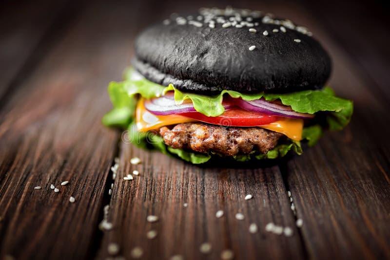 Домодельный черный бургер с сыром Cheeseburger с черной плюшкой o стоковое фото rf