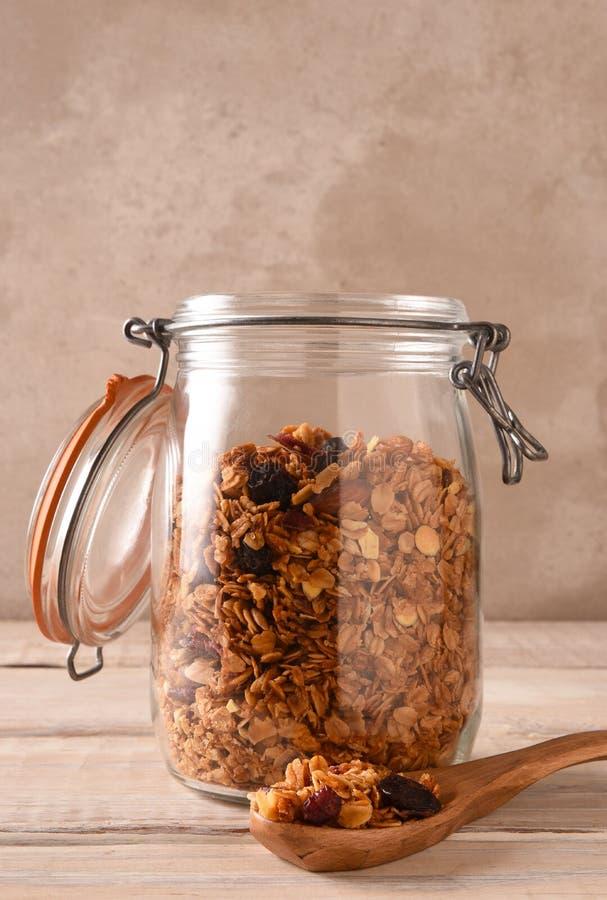 Домодельный granola в опарнике хранения с крышкой раскрывает ложку на переднем плане стоковые изображения