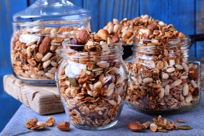 Домодельный granola с различными гайками и семенами в стеклянных опарниках стоковая фотография