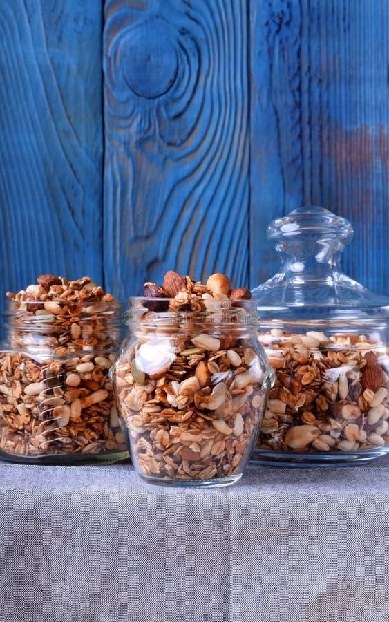 Домодельный granola с различными гайками и семенами в стеклянных опарниках стоковое фото rf