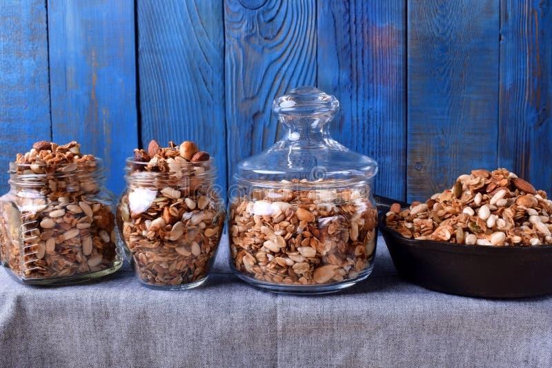 Домодельный granola с различными гайками и семенами в 3 стеклянных опарниках и одном лотке литого железа стоковые фото