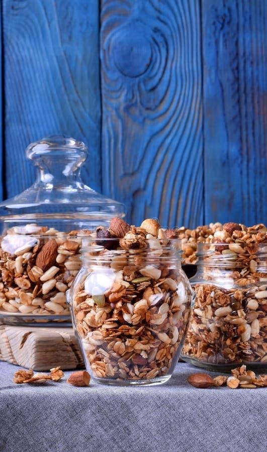 Домодельный granola с различными гайками и семенами в стеклянных опарниках стоковое изображение rf