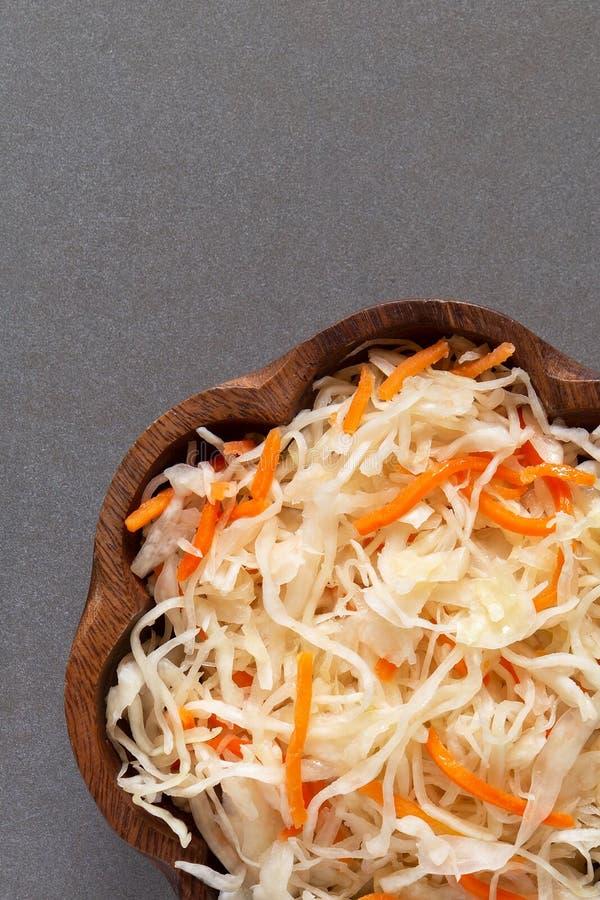 Домодельный sauerkraut с морковами в шаре на сером кухонном столе стоковое изображение rf