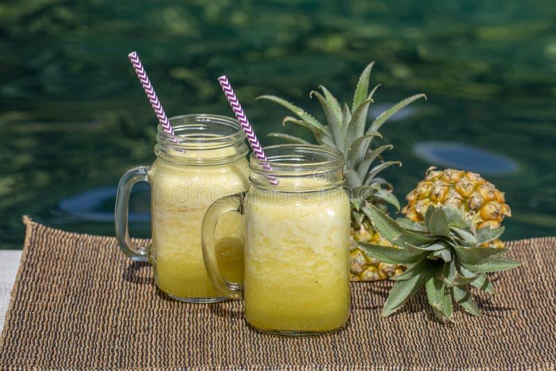 Домодельный smoothie манго и ананаса сделанный с молоком кокоса в стеклянной кружке 2 около бассейна Остров Бали, Индонезия стоковая фотография rf