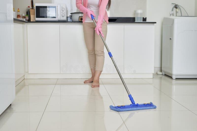 Домоустройство и концепция чистки, счастливая молодая женщина в розовых резиновых перчатках обтирая пыль используя mop пока очища стоковое изображение
