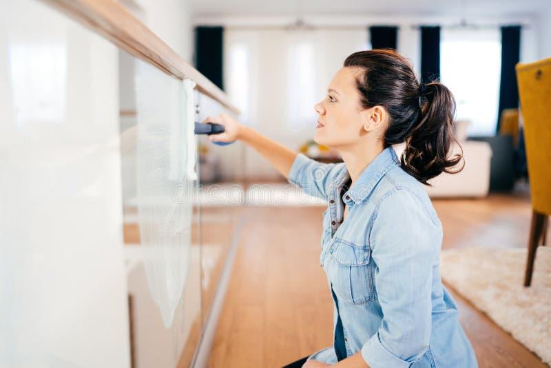 Домоустройство работает - портрет чистки женщины вокруг дома Женщина используя тензид и ткань для чистки стеклянного окна стоковые фото