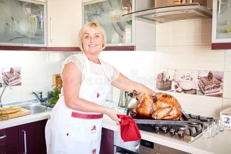 Домохозяйка варя гарнированного зажаренного в духовке индюка на рождестве на предпосылке кухни Концепция индюка благодарения стоковые изображения