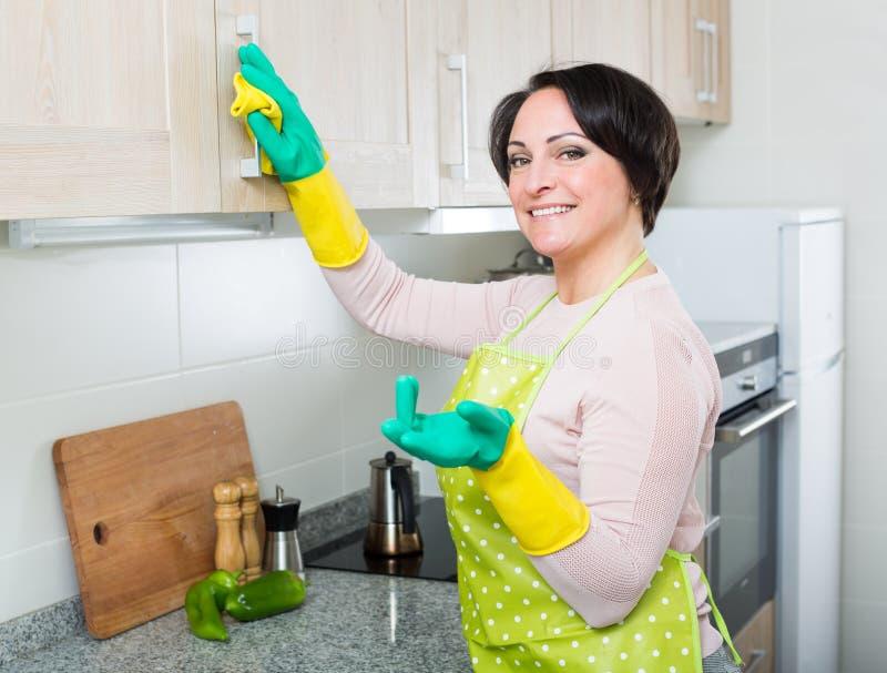 Домохозяйка извлекая пятна от кухонных шкафов в кухне стоковая фотография rf