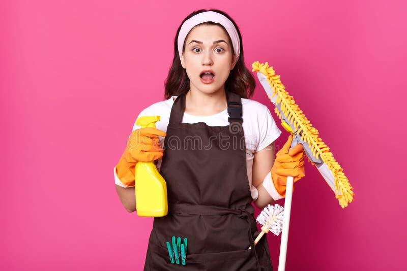 Домохозяйка находясь в панике потому что она имеет так много вещи, который нужно очистить, стоит с открытым ртом, держит детержен стоковые изображения rf
