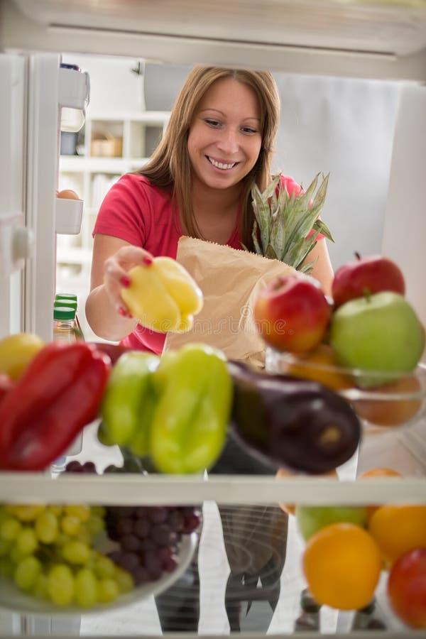 Домохозяйка находилась в рыночном мести и положенных перцах в холодильнике стоковая фотография rf