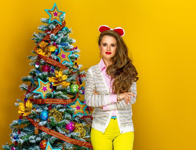 Домохозяйка около рождественской елки на желтой предпосылке стоковые фото