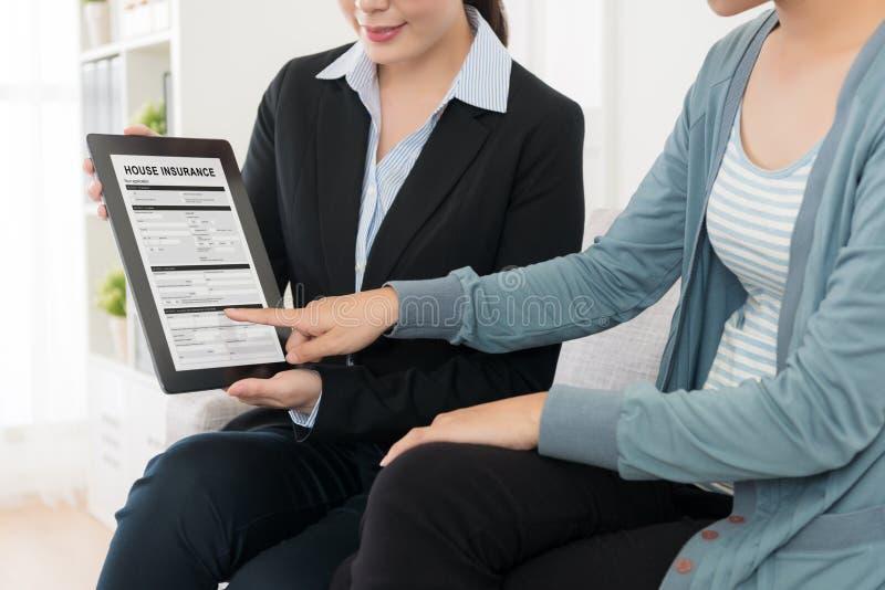 Домохозяйка подписывая к покупая страхованию дома стоковые изображения