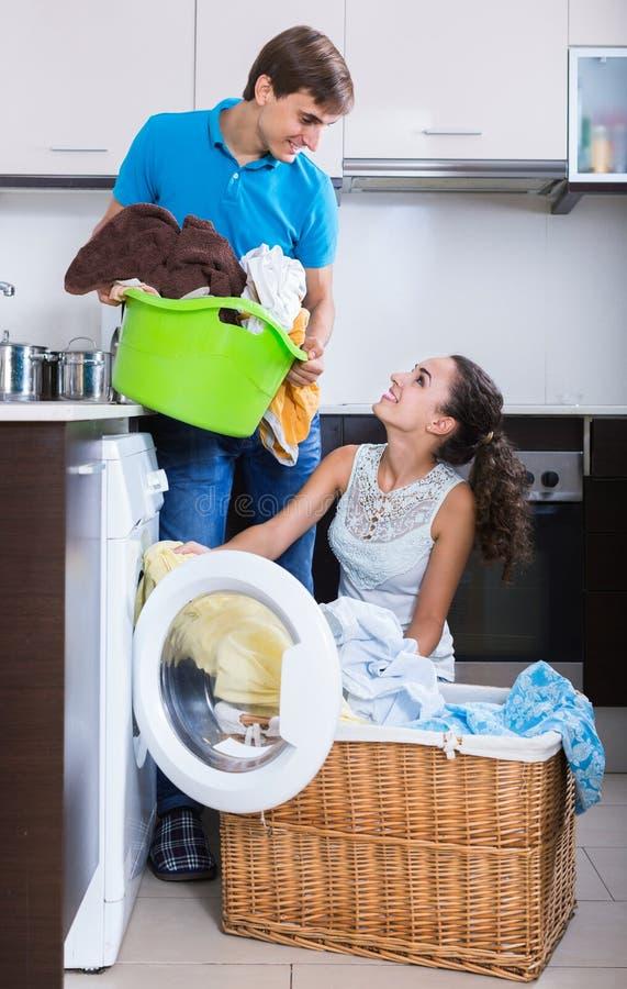 Домохозяйка порции супруга для того чтобы использовать стиральную машину внутри помещения стоковые изображения