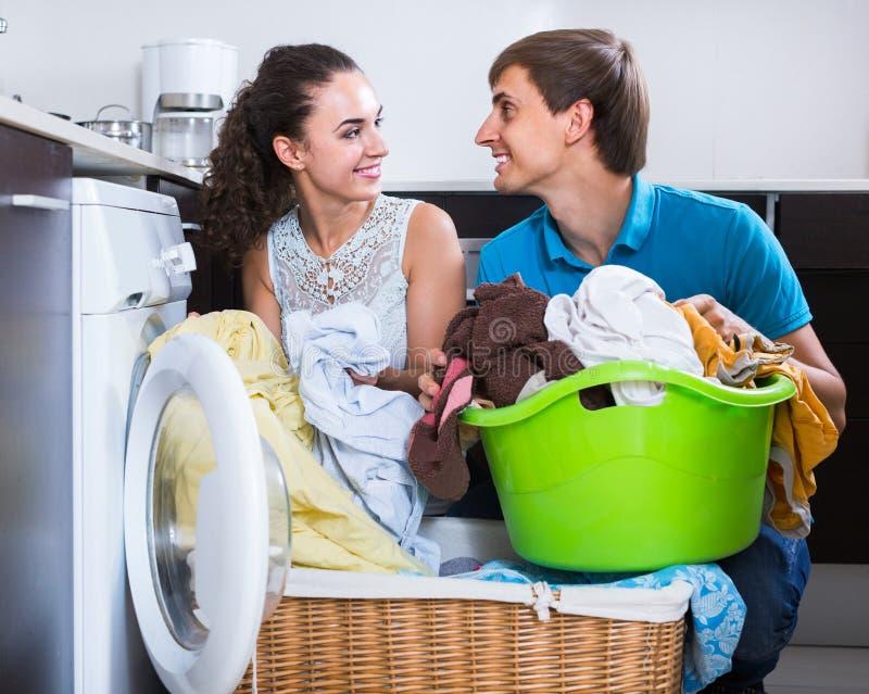Домохозяйка порции супруга для того чтобы использовать стиральную машину внутри помещения стоковые изображения rf