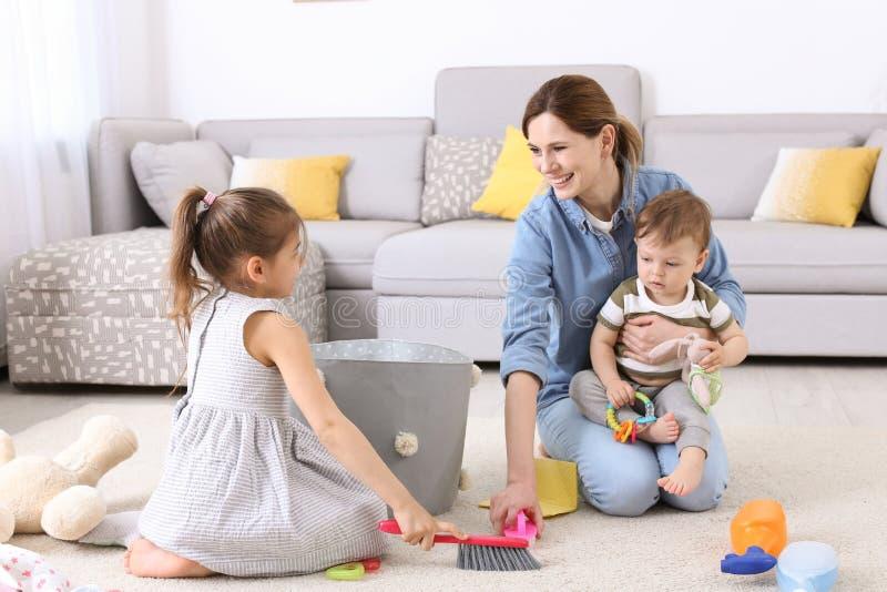 Домохозяйка при маленькие дети очищая ковер стоковое изображение rf