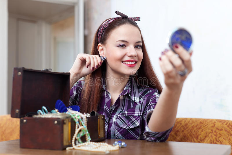 Домохозяйка пробует серьги в доме стоковое изображение
