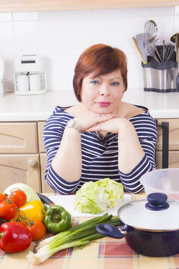 Домохозяйка среднего возраста варя овощи стоковая фотография rf