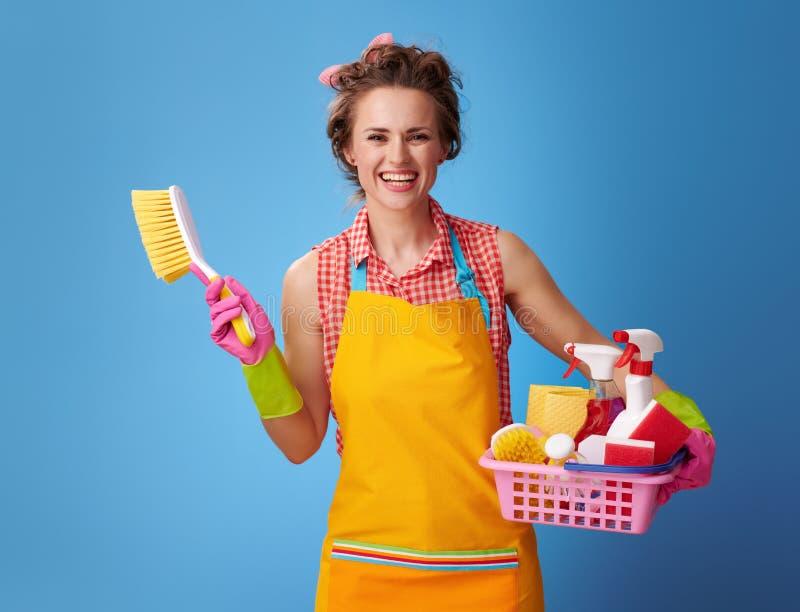 Домохозяйка с корзиной поставек и щетки чистки на сини стоковые изображения