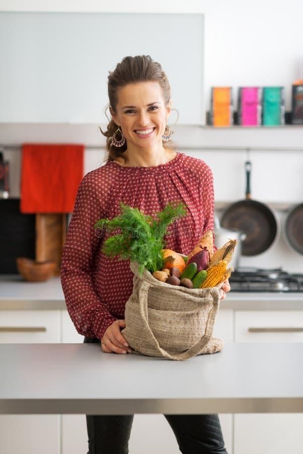 Домохозяйка с приобретениями местного рынка в кухне стоковое изображение