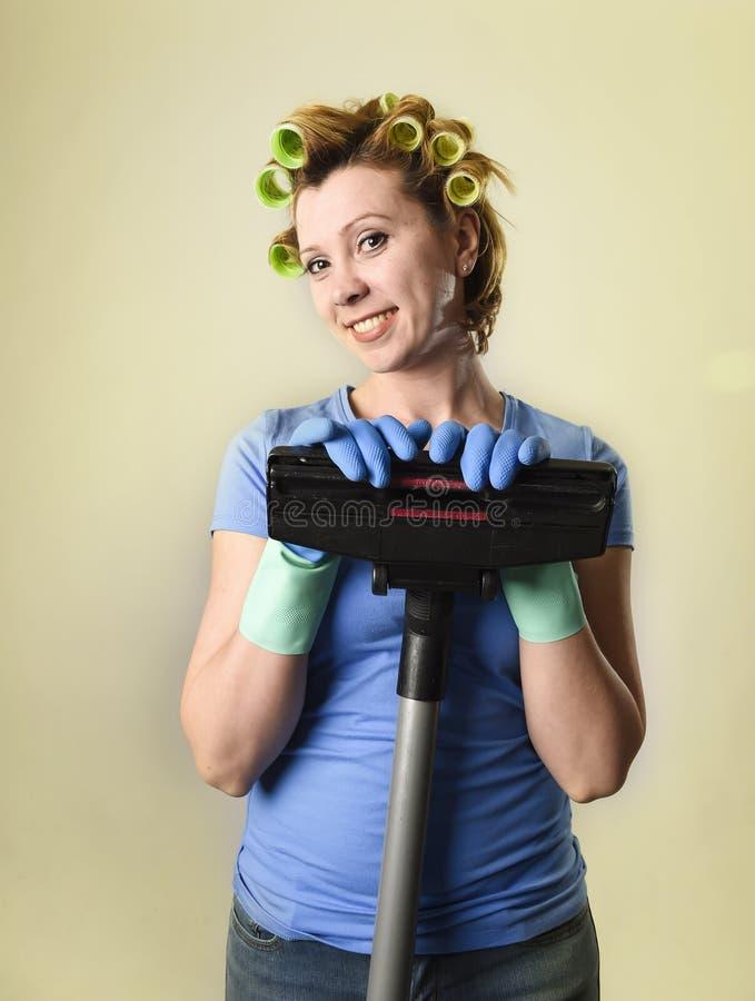 Домохозяйка с роликами волос и пылесосом перчаток счастливым усмехаясь жизнерадостным держа стоковые фото