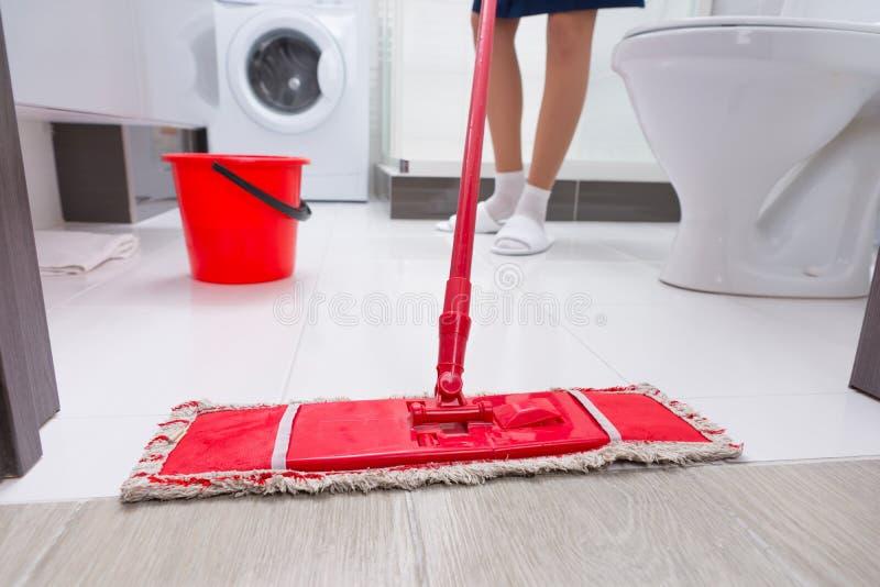 Домохозяйка mopping пол в ванной комнате стоковые изображения
