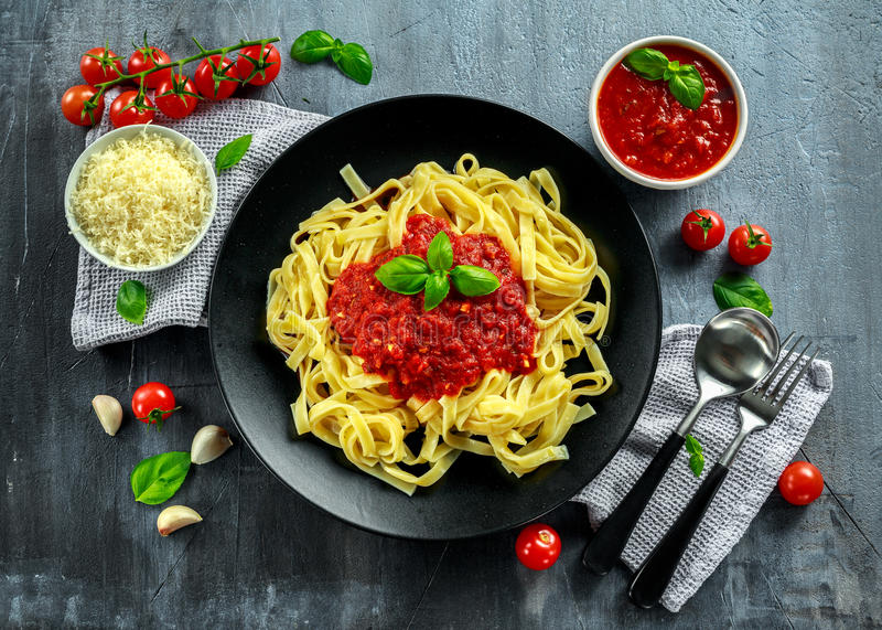 Домодельные горячие макаронные изделия с соусом Marinara, базиликом, чесноком, томатами, сыр пармесаном на плите стоковое фото rf