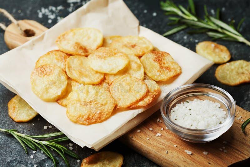 Домодельные картофельные стружки с солью и травой моря на разделочной доске стоковое изображение