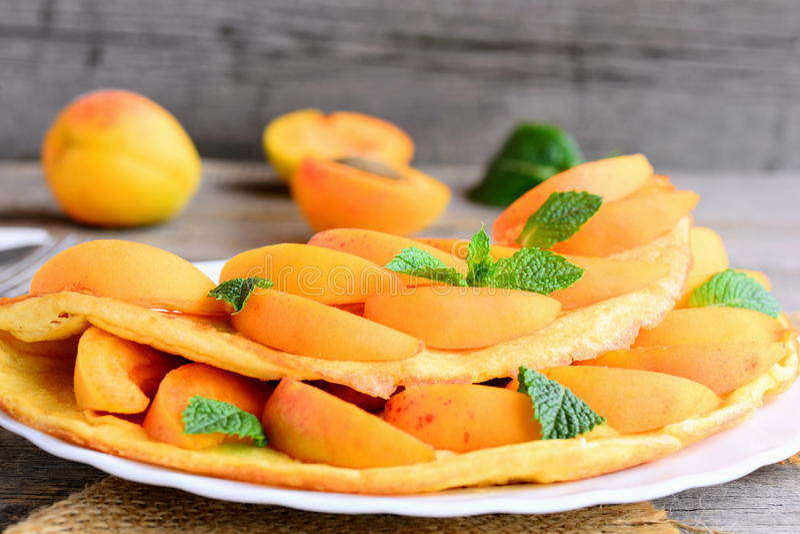 Домодельные омлет или омлет заполненные с свежими кусками и мятой абрикоса на белой плите сервировки Как сделать омлет стоковое изображение