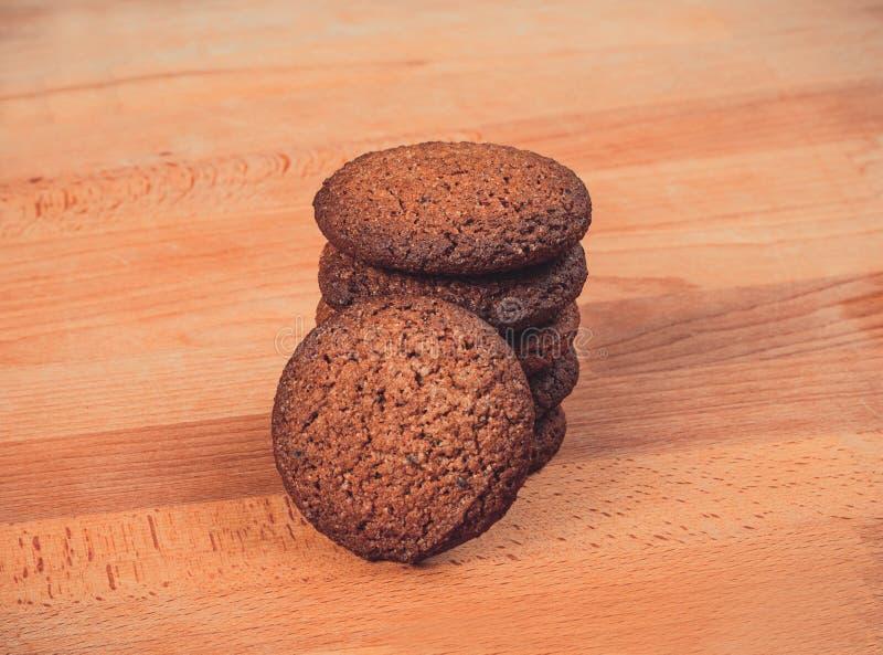 Домодельные печенья овса на деревянной предпосылке Печенья овсяной каши на старой деревянной разделочной доске стоковое изображение