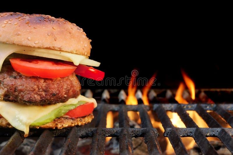 Домодельный бургер говядины BBQ на горячем пламенеющем гриле стоковые фотографии rf