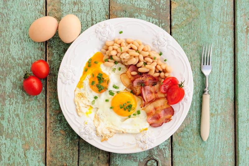 Домодельный завтрак яичниц, бекона, фасолей и томатов на w стоковое фото