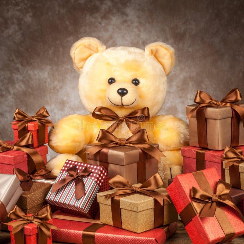 Домодельный плюшевый медвежонок и много коробки с подарками на старой горжетке стоковое фото