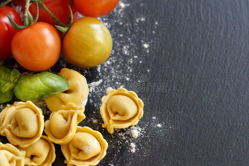 Домодельный сырцовый tortellini с свежими томатами и базиликом стоковое фото