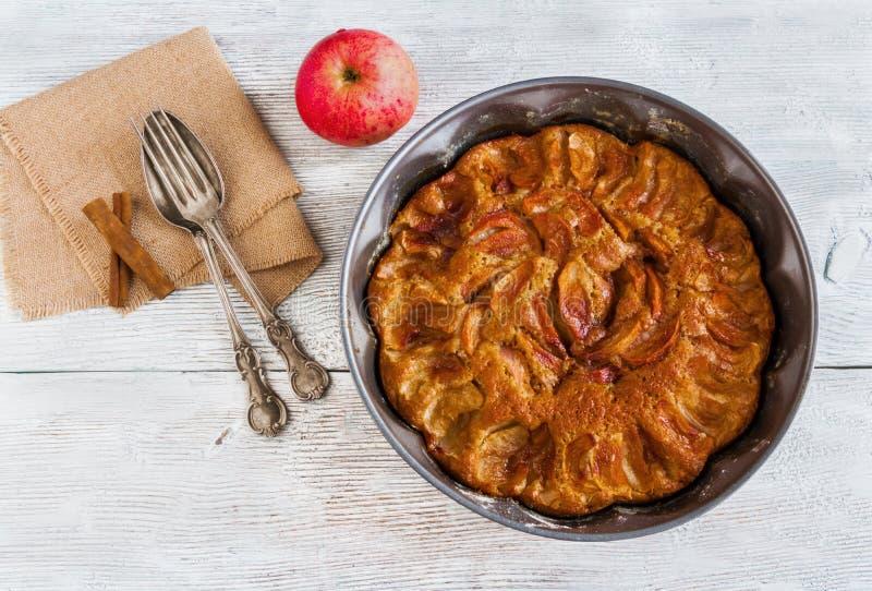 Домодельный торт яблока и циннамона Пирог в блюде выпечки, винтажной вилке и ложке и свежих фруктах на деревянной предпосылке Взг стоковые изображения