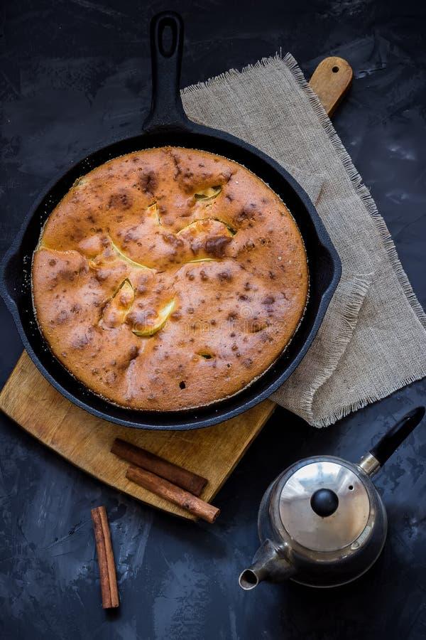 Домодельный яблочный пирог в лотке утюга года сбора винограда и баке чая на темной предпосылке стоковое фото rf