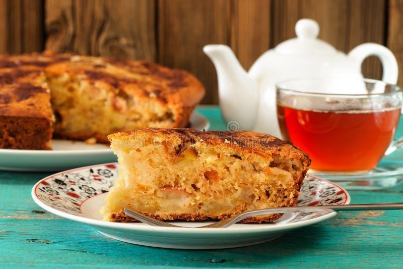 Домодельный yummy яблочный пирог, черный чай и чайник белизны на turquois стоковые изображения