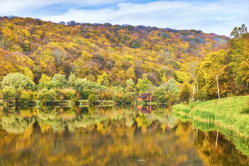 Дом 's рыболова на озере в лесе осени стоковое фото