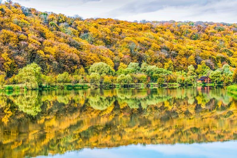 Дом 's рыболова на озере в лесе осени стоковая фотография rf