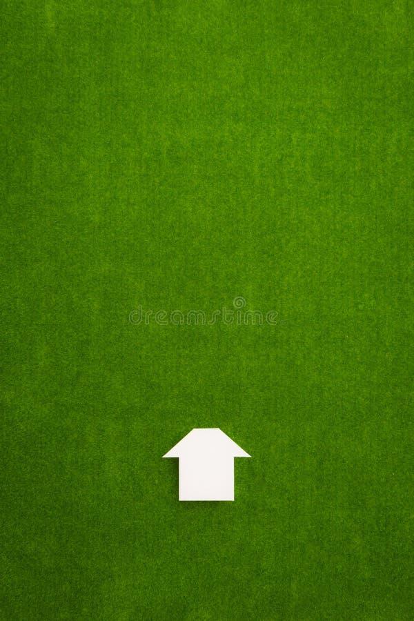 Дом белого значка простой на зеленой предпосылке бархата стоковое изображение