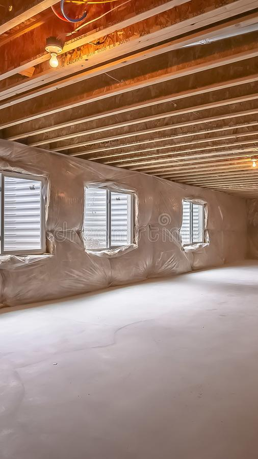 Дом вертикальной рамки новый под конструкцией с окнами установленными на пластиковую покрытую стену стоковая фотография rf