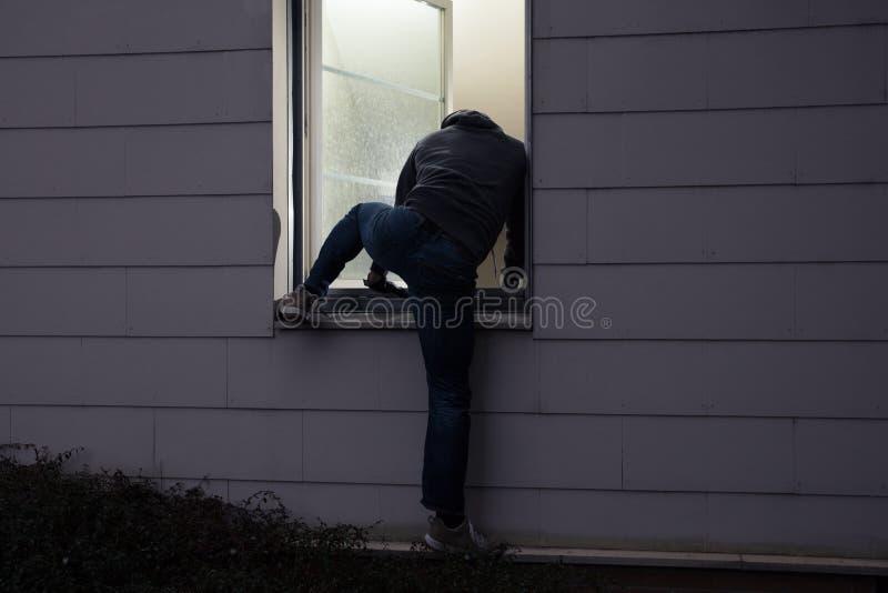 Дом взломщика входя в через окно стоковые фотографии rf
