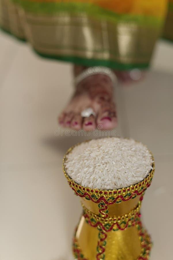 Дом входя в groom индийской индусской невесты после wedding путем нажатие бака заполнил с рисом с ее ногой. стоковое изображение rf