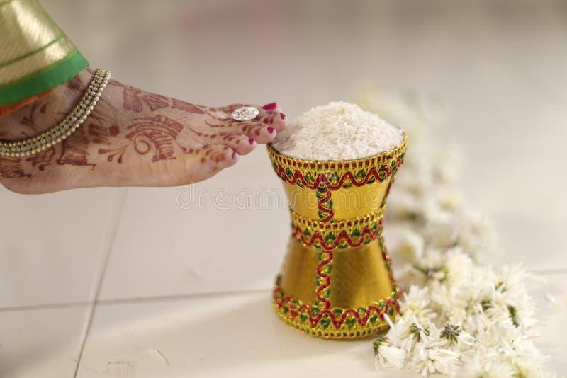 Дом входя в groom индийской индусской невесты после wedding путем нажатие бака заполнил с рисом с ее ногой. стоковое фото rf