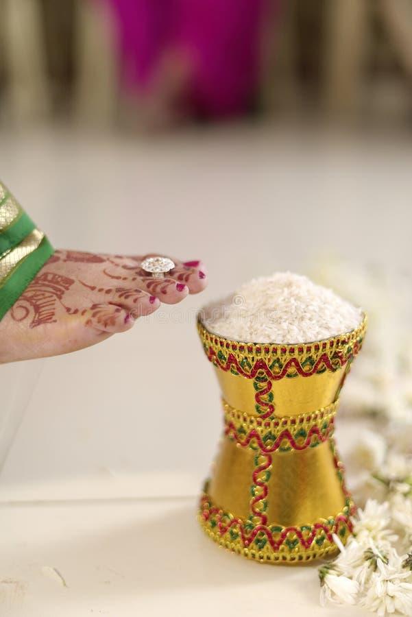 Дом входя в groom индийской индусской невесты после wedding путем нажатие бака заполнил с рисом с ее ногой. стоковые фотографии rf
