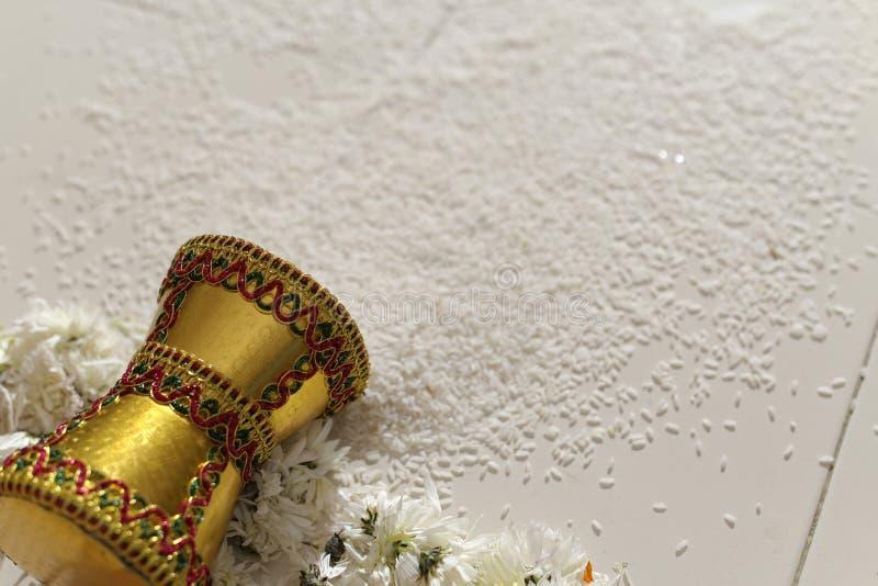 Дом входя в groom индийской индусской невесты после wedding путем нажатие бака заполнил с рисом с ее ногой. стоковая фотография
