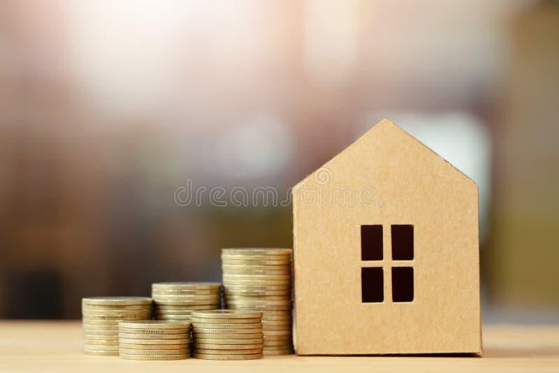Дом в коричневых повторно использованных бумажных монетках модели и денег штабелированных на одине другого в различных положениях стоковые изображения