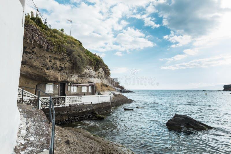 Дом в пещере как раз перед океанскими волнами естественный альтернативный способ жить на месте побережья необыкновенном для постр стоковые фото