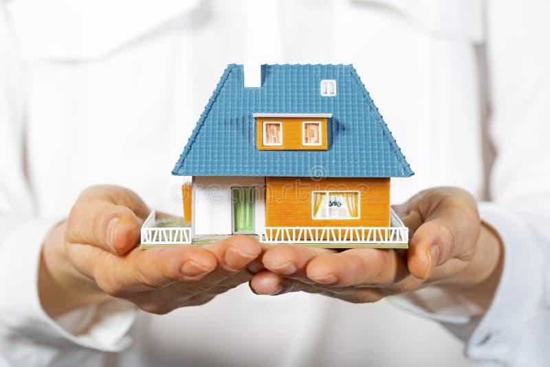 Дом в человеческих руках, концепция новой недвижимости стоковое фото rf