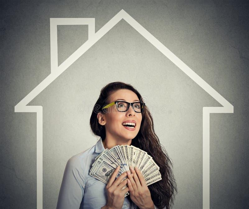 Дом, деньги, концепция людей Успешная бизнес-леди держа деньги наличных денег доллара стоковое изображение rf